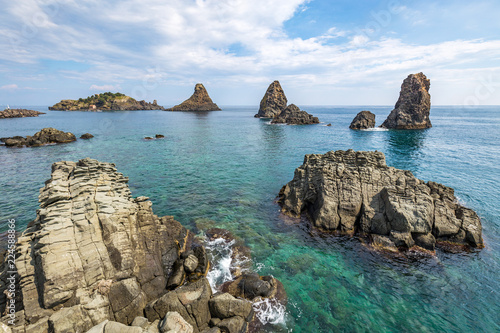 View on the rocky islands in Aci Trezza, Sicily, Italy, with the Islands of the Cyclops in the background Poster Mural XXL