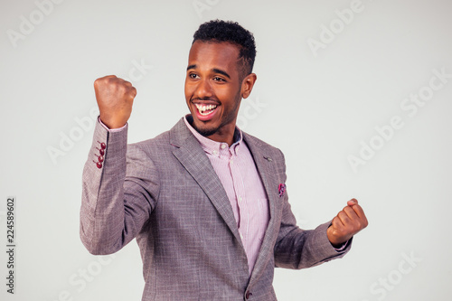 Cuadros en Lienzo  handsome young Afro American businessman in classic suit rejoicing and exulting