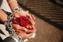 Man And Woman, Bride And Groom Hold Lock, Their Hands Are Wrapped In Chains. Concept Together Forever, Commitment, Reliability, Devotion.