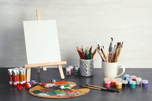 Easel With Various Artist Tools On Table Against Light Wall. Space For Text