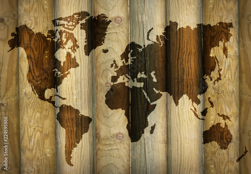Shadow of a world map projecting on wooden planks as a background