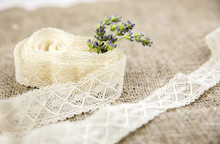 Arts And Crafts Background Concept. Bunch On Cut Fresh Lavender Branches Sticking Out Of A Cotton Lace Roll, Burlap Cloth On Background.