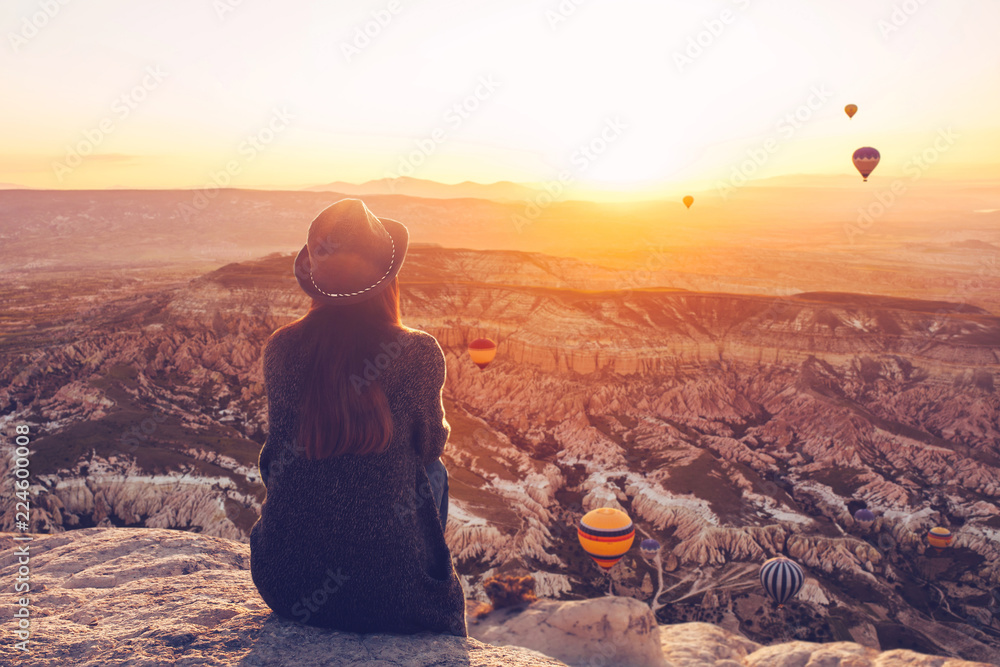 Fototapety, obrazy: A girl in a hat on top of a hill in silence and loneliness admires the calm natural landscape and balloons.