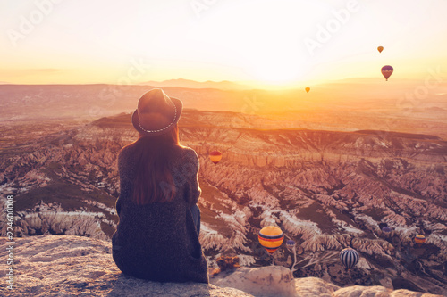 Cuadros en Lienzo A girl in a hat on top of a hill in silence and loneliness admires the calm natural landscape and balloons