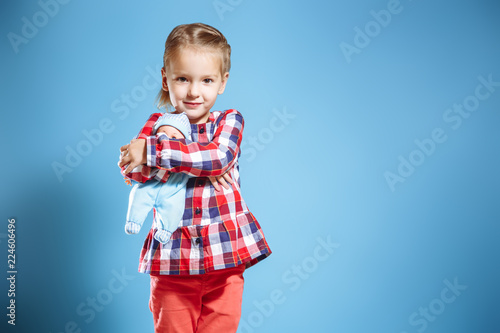 Fotografia Cute little girl with doll on blue background