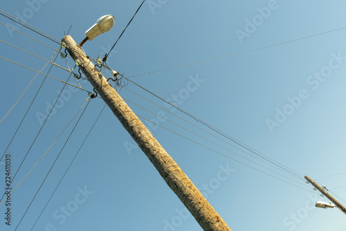 Fotografie, Obraz  pole with wires of a power line with a lantern on a blue sky background