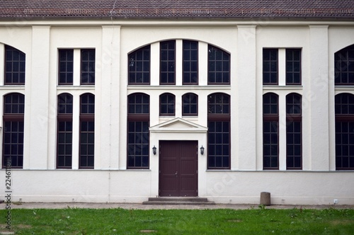 In de dag Theater an old white house with big windows and a brown door