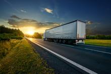 Truck Driving On The Asphalt Road In Rural Landscape At Sunset