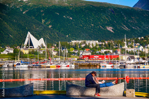 A couple sits on a bench in front of the calm, picturesque harbor at Tromso in far northern Norway in summer, with colorful boats and the Arctic Cathedral in the background