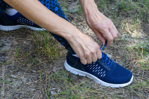 Fotografía  Young fitness woman runner tying shoelace on forest trail