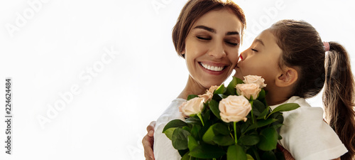 Family. Love. Holiday. Mom and daughter. Girl is giving a bouquet for her mother and kissing her, woman is smiling; at home