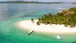 Aerial rising drone shot away from a beautiful, white sand isle, palm trees and Paraw boats, at Pass island, in Philippines