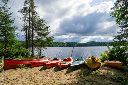 Fototapeta Kayaks and a canoe by the Indian lake in upstate NY (USA)