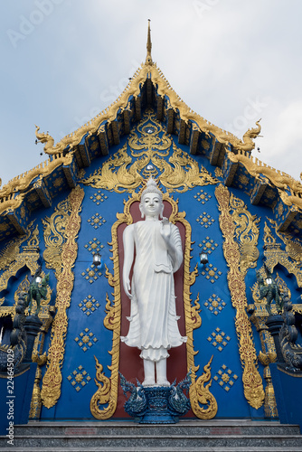 Deurstickers Bedehuis From below show of white Buddha statue in design of Wat Rong Suea Ten (also known as Blue Temple) with golden ornaments, Thailand