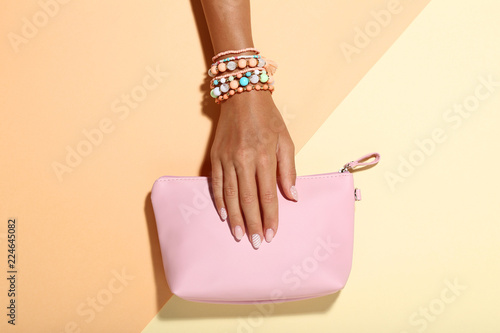 Tableau sur Toile Female hand with bracelets and handbag on colorful background