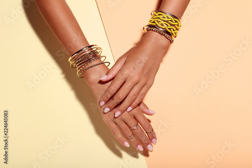 Female hands with bracelets and rings on colorful background Poster Mural XXL