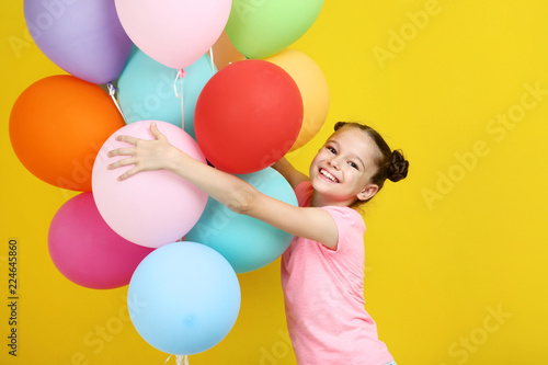 Fotografía  Beautiful young girl with colored balloons on yellow background