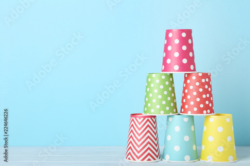 Colorful paper cups on blue background