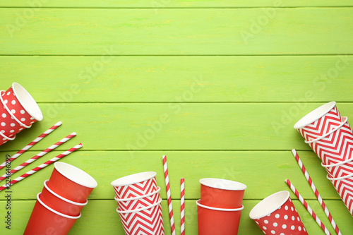 Red paper cups with straws on green wooden table