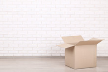 Cardboard Box On Brick Wall Background