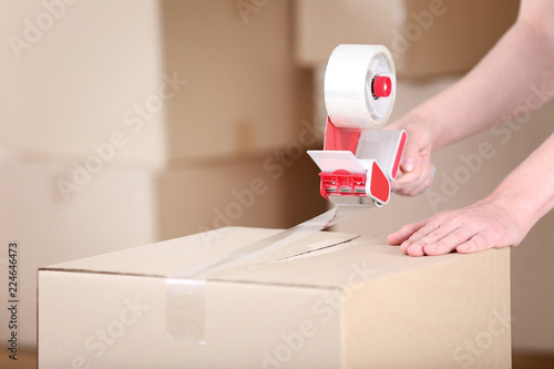 Fotografía  Female hands packaging cardboard box with dispenser