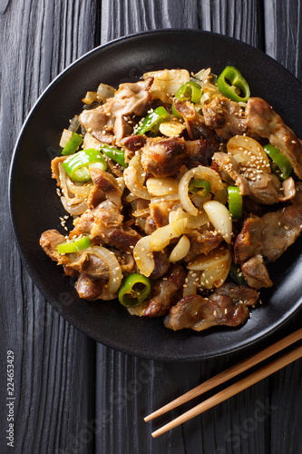 Dak-ttongjip is a Korean dish made by stir-frying chicken gizzard with spices close-up on a plate. Vertical top view