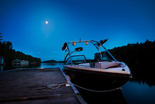 A Wakeboard Boat Docked On Lake Joseph In The Evening With The Moon In The Background.