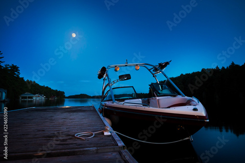 Photo A wakeboard boat docked on Lake Joseph in the evening with the moon in the background