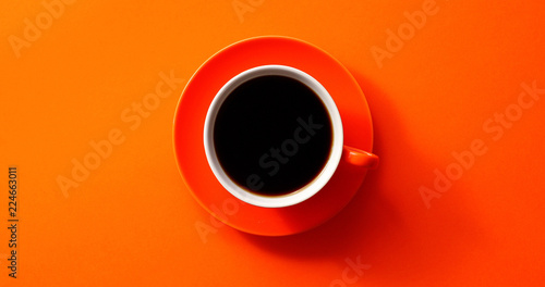 From above view of cup with black coffee placed on orange background
