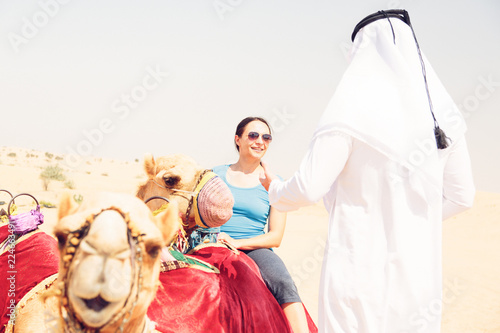 Fotografia, Obraz  Arabian Man And Tourist Riding A Camel