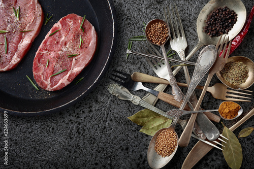 Raw pork in pan and various herbs and spices.