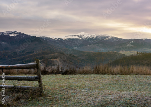 wooden fence on meadow with frozen grass. mysterious late autumn scenery with snow on tops of distant mountains