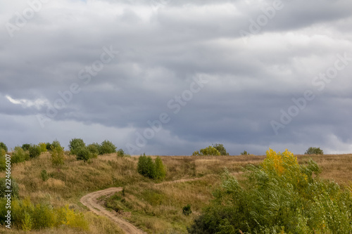 Poster Donkergrijs A rural dirt road in the hill among the autumn landscape and large clouds.