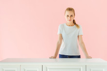 Attractive Young Woman Standing Behind Kitchen Table Isolated On Pink