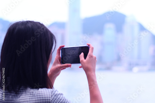 Photo  Woman is taking photo with smart phone of city view in Hong Kong.