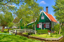 Traditional Green Dutch House With Little Wooden Bridge Against Blue Sky In The Zaanse Schans Village, Netherlands. Famous Tourism Place