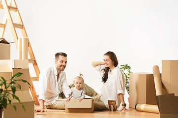 Obraz Couple moving to a new home. Happy married people with newborn child buy a new apartment to start life together. The family at repair and relocation planing to accommodation against boxes
