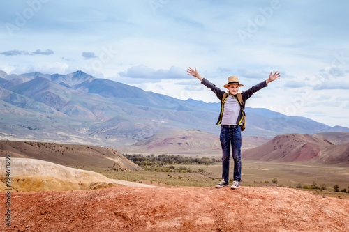Stickers pour porte Orange eclat Happy boy traveler with his hands up on blue mountains background