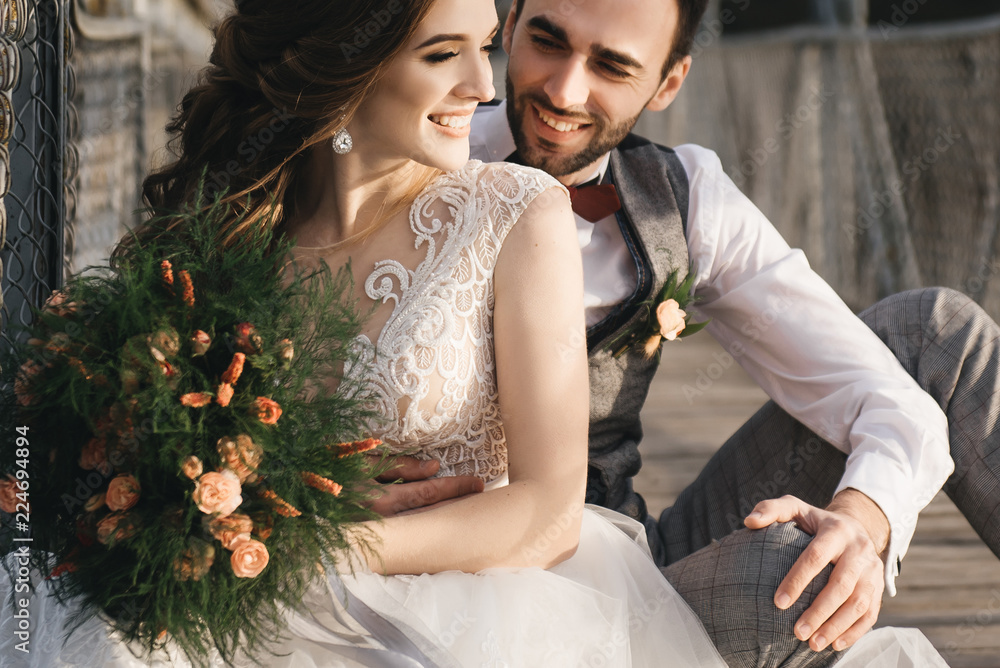 Fototapety, obrazy: Happy young smiling bride and groom are sitting on the suspension bridge. Sunny wedding photos in an interesting place