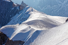 Chamonix, South-east France, Auvergne-Rhône-Alpes. Climbers Heading For Mont Blanc. Descending From Aiguille Du Midi Cable Car Station Towards Sunny Snow Planes And Glaciers On Border Of France