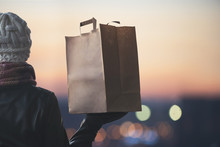 A Woman In A Winter Clothes With A Paper Bag On The Background Of The Evening City. 24 Hours Delivery. Concept