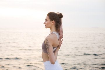 Fototapeta na wymiar Beautiful girl in sporty top and white leggings holding hands behind back with sea view on background. Young woman dreamily looking aside while practicing  yoga by the sea