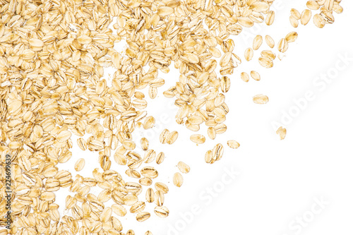 Lot of whole flat raw rolled oats left upper corner isolated on white background Canvas Print