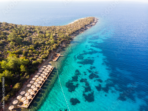 Fotografering  Aerial View of Peninsula Beach Cove with Sunbeds Blue Sea and Trees in Bodrum Yali Turkey