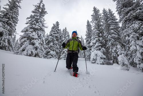 Fotografie, Obraz  Smiling adventurer is walking snowshoeing