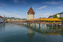 The Famous Kapellbrucke (Chapel Bridge) Wooden Footbridge Across The Reuss River In The City Of Lucern, Switzerland.