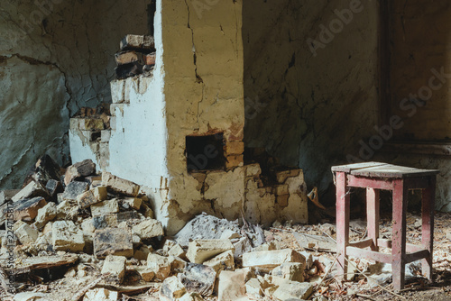 Fotografia  abandoned building with broken brick wall and wooden chair with dust