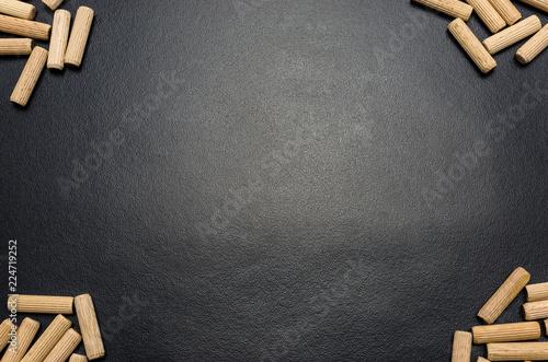Fotografie, Obraz  A lot of wooden pegs lying flat on a black background.