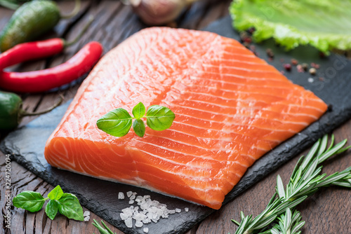 Fresh salmon fillet on black cutting board with herbs and spices.