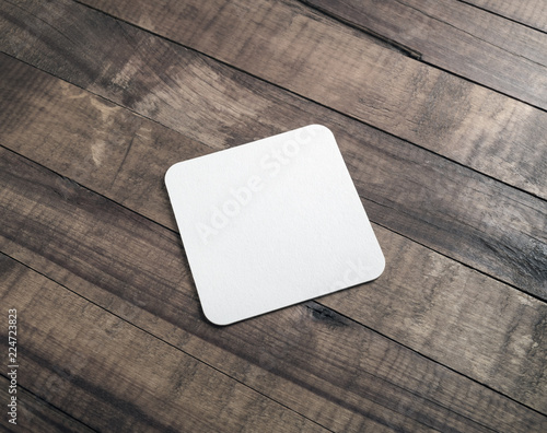 Square beer coaster on wooden background.